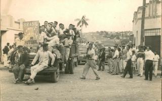 Comemoração pela vitória da Copa do Mundo de Futebol de 1958 pelo Brasil - em primeiro plano, muitos homens, alguns músicos, como Waldemar Lima e Cornélio Bicalho, sobre caminhões, outros homens de pé na esquina, ao fundo a Rua Palestina