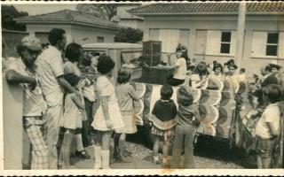 Carro alegórico sobre telefonia em desfile cívico, rodeado por pessoas e crianças, Vê-se, à direita, o fotógrafo Afonso Souza. Ano 1960-1969