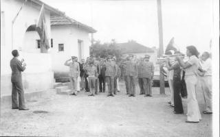 Solenidade de hasteamento da bandeira nacional, com um batalhão de policiais militares em continência e a Band Lira Santo Antônio à direita. Entre os músicos, vê-se Vicente de Paula Leandro (Paulinho), e José Bicalho.   1960-1969