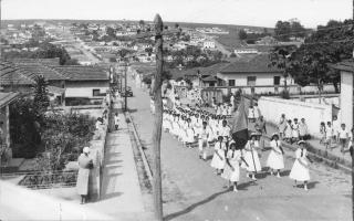Desfile de estudantes do Educandário Dom Alexandre, vendo-se os bairros Santa Terezinha e Camposaltinhos. 1950-1959