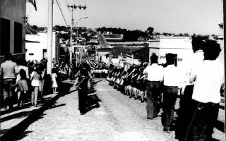 Desfile cívico pela Rua Cel. Frederico Franco, vendo-se muitas pessoas de costas, entre elas Waldemar Lima tocando trombone. 1970-1979