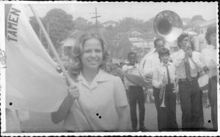 Ana Amélia Leão segurando a bandeira mineira, com a Banda Lira Santo Antônio à direita. 1970-1979