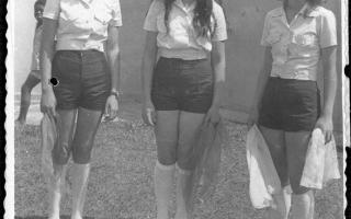 Desfile cívico, Gentil, Aparecida e Irani, em uniforme de desfile cívico, segurando pano. 1970-1979
