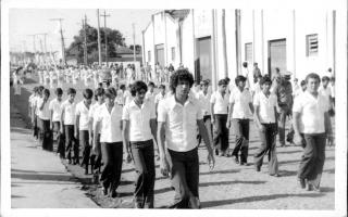 'Estudantes em desfile cívico pela Rua Tiradentes, vendo-se ao fundo os barracões da Cooperativa Agropecuária 1960 a 1979
