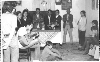 'Grupo reunido em torno de cantor com violão, vendo-se ao fundo Leônidas, Chico Raimundo, Diogo e Donizete 1960 a 1969