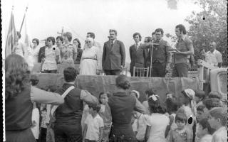 'Autoridades da sociedade civil sobre palanque, entre elas Iolanda Domingos, Laurici, Weber, Maria Augusta, Madre Emanuelle Favale, Chico Raimundo, Vantuilm Vicente Paulo e Zé Aroldo. No chão, crianças e membros da fanfarra 1960 a 1969
