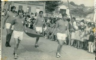 'Paulo Rubens, Guenê, Julinho e Eurípedes em desfile pela Rua Palestina, na altura da Praça Benedito  Valadares, vendo-se ao fundo edificações demolidas, como a Casa Domingos e uma residência, além de uma multidão assistindo ao desfile 1970 a 1979