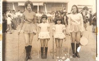 'Adelina, Lídia, Dione, Roseli Campos com trajes de baliza em desfile cívico na Praça Benedito Valadares, vendo-se multidão ao fundo 1960 a 1979