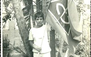 'Estudante segurando bandeira do Educandário Dom Alexandre no jardim da mesma instituição 1960 a 1979