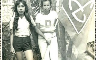 'Estudantes Lúcia e Célia segurando bandeira do Educandário Dom Alexandre no jardim da mesma instituição 1960 a 1979