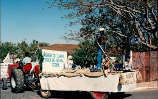 Carro alegórico alusivo ao trabalho na cafeicultura, com um homem negro segurando uma vassoura de café, com um pequeno pé de café sobre o carro alegórico puxado por um trator. 2000-2004