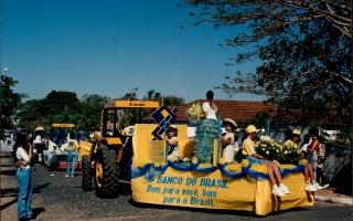 Desfile de carros alegóricos durante comemoração do cinquentenário da emancipação do município, vendo-se em primeiro plano um carro alegórico alusivo ao Banco do Brasil, com meninas segurando flores, seguindo outros carros alegóricos pela rua. 1994