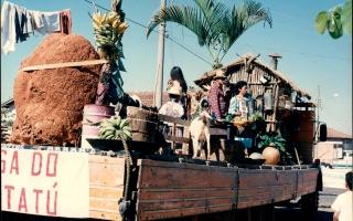 Carro alegórico alusivo à roça do personagem Jeca Tatú, com um cupim, cachos de banana, casebre e umacabra sobre caminhão, vendo-se Kênia, Mario e Betânia, entre outroas pessoas, durante o desfile em comemoração ao cinquentenário da emancipação política do município, 1994