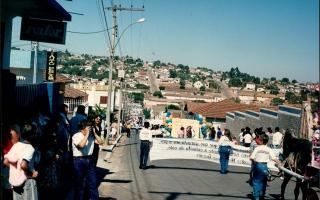 Desfile cívico descendo a Rua Cel. Frederico Franco, vendo-se o casario da cidade e uma grande aglomeração de pessoas em comemoração ao cinquentenário da emancipação política do município. 1994
