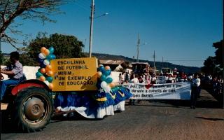 Desfile cívico em comemoração ao cinquentenário da emancipação política do município, vendo-se, em primeiro plano, um carro alegórico alusivo à Escolinha de Futebol Mirim, e ao fundo, muitas pessoas em desfile. 1994